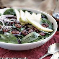 Spinach Salad with Pears, Cranberries and Candied Pecans in a white ceramic serving bowl