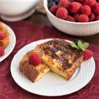 Sugar-Crusted French Toast cut in half and garnished with berries and mint on a white plate