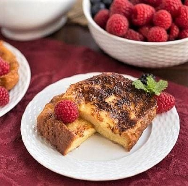 Sugar-Crusted French Toast Recipe cut in half and garnished with berries and mint on a white plate