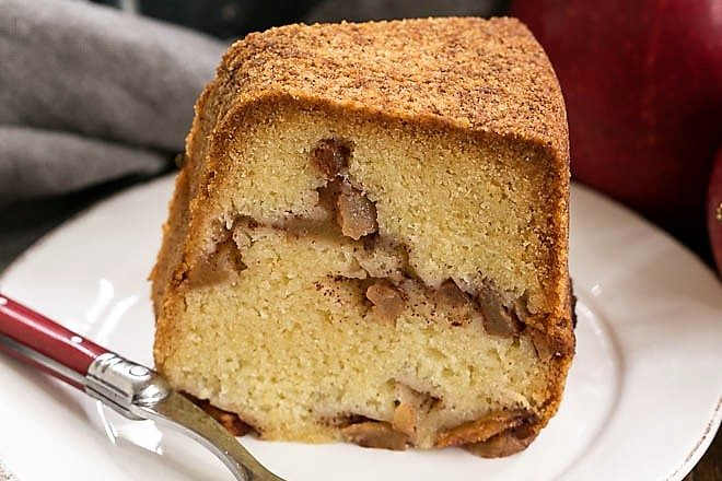Cinnamon Apple Bundt cake slice on a round white plate with a fork
