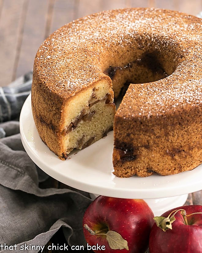 Cinnamon apple bundt cake on a white cake stand with a slice removed.