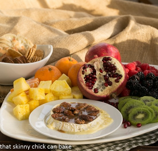 baked Camembert cheese on a platter with fresh fruit and crackers