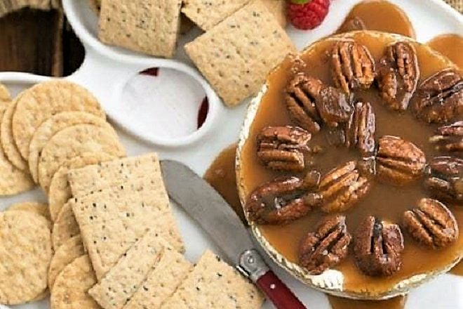 overhead image of cheese tray with Baked Camembert with Caramel and Pecans alongside crackers for serving
