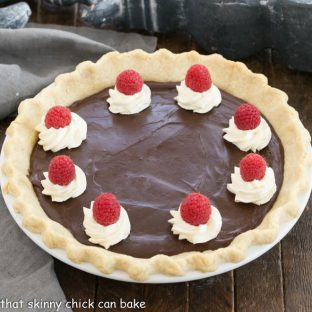 Overhead view of chocolate cream pie topped with whipped cream swirls, raspberries