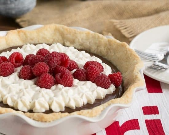 Chocolate Cream Pie in a white pie dish topped with cream and berries