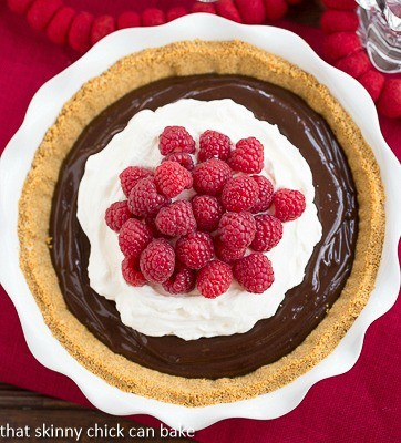 Chocolate Satin Pie in a ceramic pie plate topped with whipped cream and raspberries