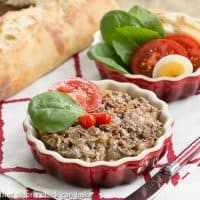Chopped liver in a shallow red ceramic dish, topped with a spinach leaf and tomato slice.