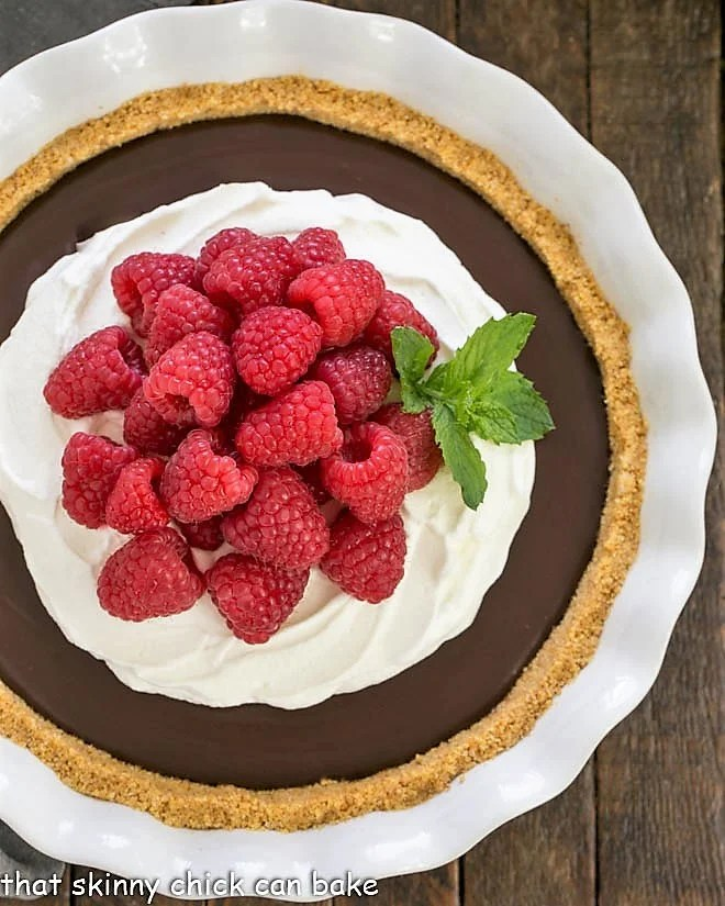 Overhead view of dark chocolate satin pie in a ceramic pie plate topped with raspberries and whipped cream