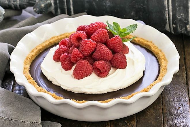 side view of chocolate satin pie in a white pie plate