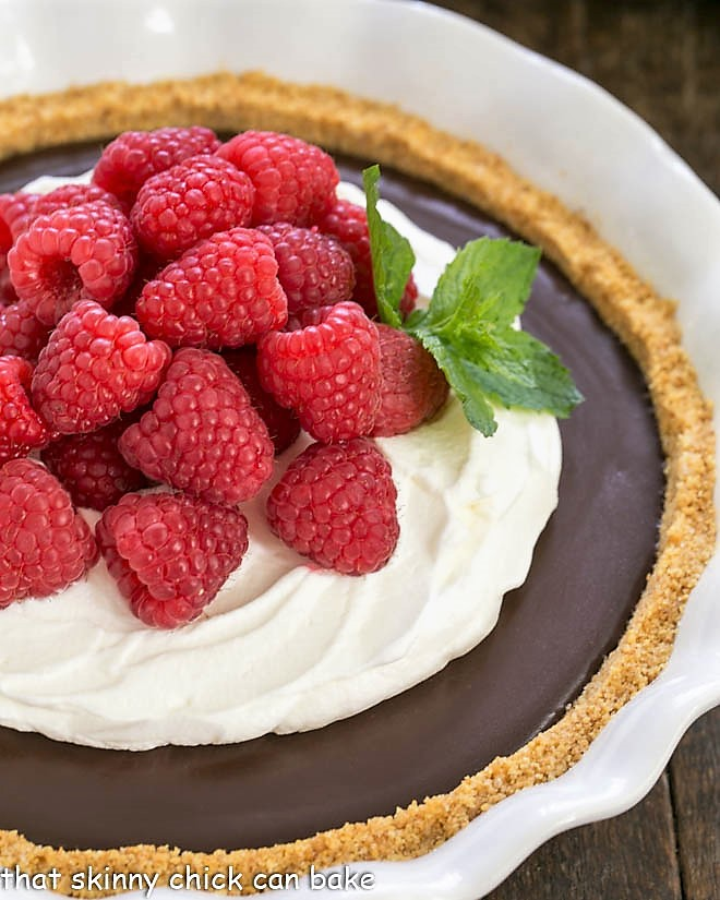 Close view of the chocolate pie topped with whipped cream and berries and garnished with a sprig of mint