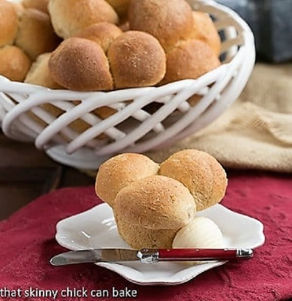 Honey Whole Wheat Cloverleaf Rolls in a basket behind one roll on a white plate