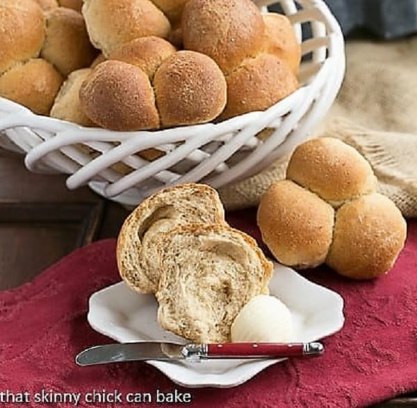 Honey Whole Wheat roll on a white plate, broken open with a pat of butter and a red handled knife