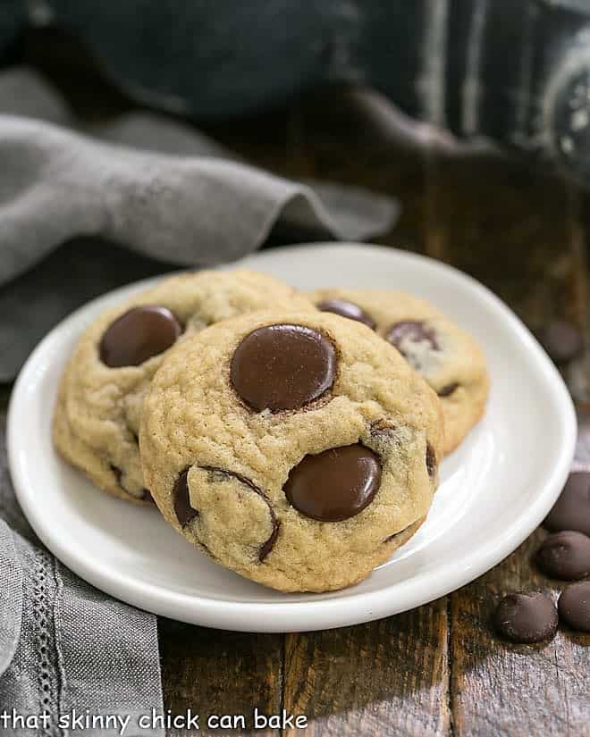 Three Chewy chocolate chunk Cookies on a round white dessert plate