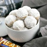 Mexican Wedding Cookies with Toffee bits in a white serving bowl with a Heath bar