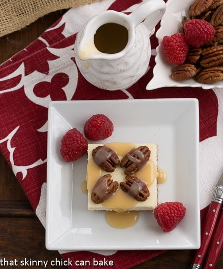 Overhead view of Caramel Pecan Cheesecake Bars on a square white plate garnished with raspberries