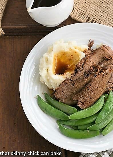 Coffee Glazed Brisket with sugar snap peas and mashed potatoes on a white plate viewed from above