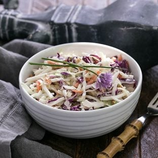 Cabbage slaw in a white bowl with a bamboo handle fork