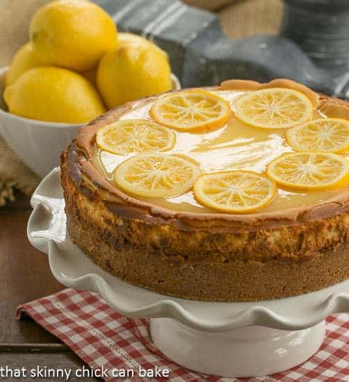 Lemon Bar Cheesecake topped with lemon slices on a white cake stand