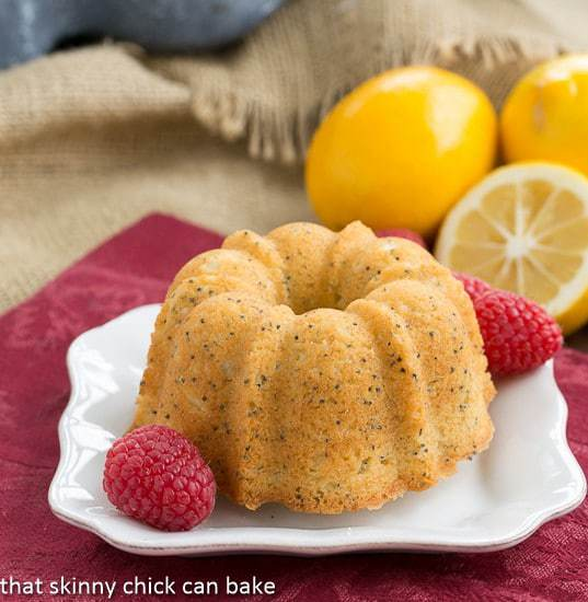 Meyer Lemon Poppy Seed Tea Cake on a white plate garnished with raspberries