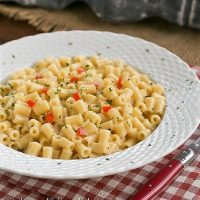 Bowl of pasta risotto with a red handled fork on a checkered napkin