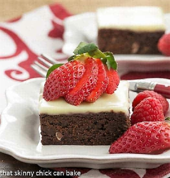 Quintuple Chocolate Brownie on a white plate with a fanned strawberry garnish