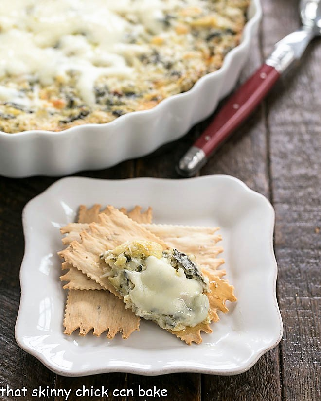 A spoonful of Hot Spinach and Artichoke Dip on an appetizer plate with crackers
