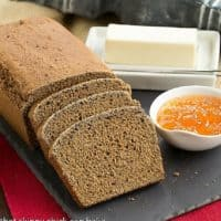 Whole Wheat Molasses Quick Bread, sliced on a slate tray with a bowl of jam and butter