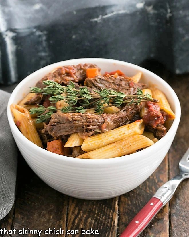 Beef Burgundy pasta in a white bowl with a fork