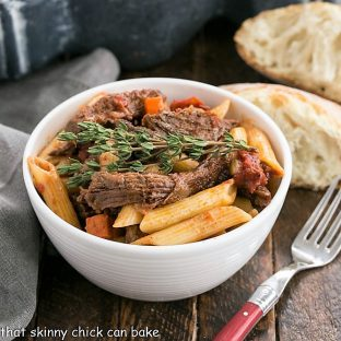 Beef Burgundy Pasta in a small white bowl with a red handled fork