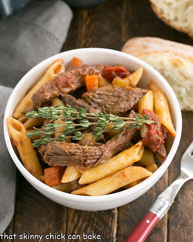 Beef Ragu with penne pasta in a white bowl with bread slice and a fork