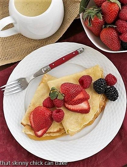 Overhead view of Butter and Rum Crêpes on a white plate with a red handled fork