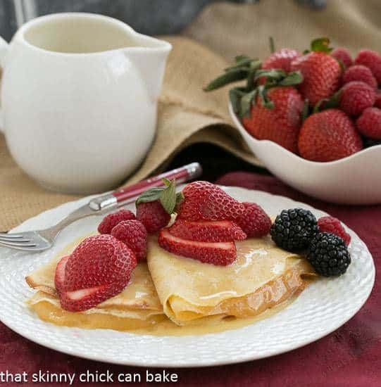 Butter and Rum Crêpes on a white plate topped with fresh berries