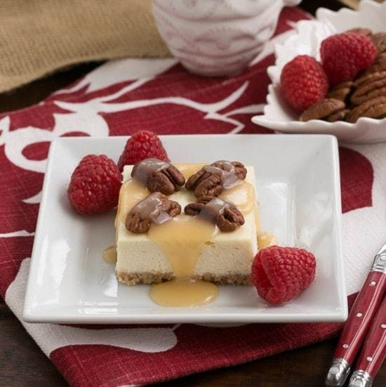 Caramel Pecan Cheesecake Bars drizzled with caramel and topped with pecans on a a square, white ceramic plate