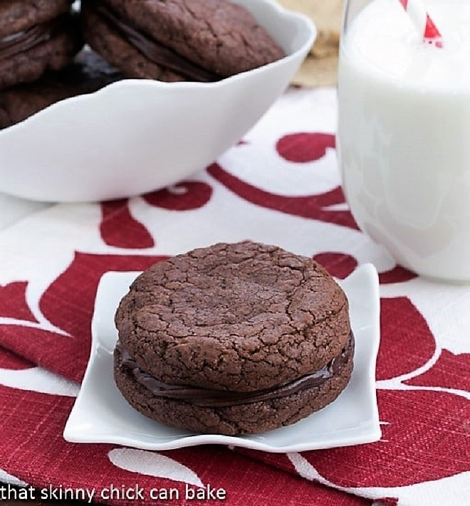 One chocolate sandwich cookie aon a white plate with a glass of milk