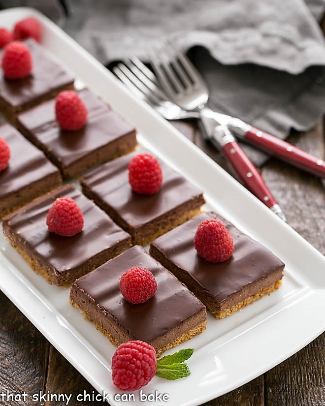 Dark Chocolate Dessert Bars on a white tray garnished with raspberries and mint