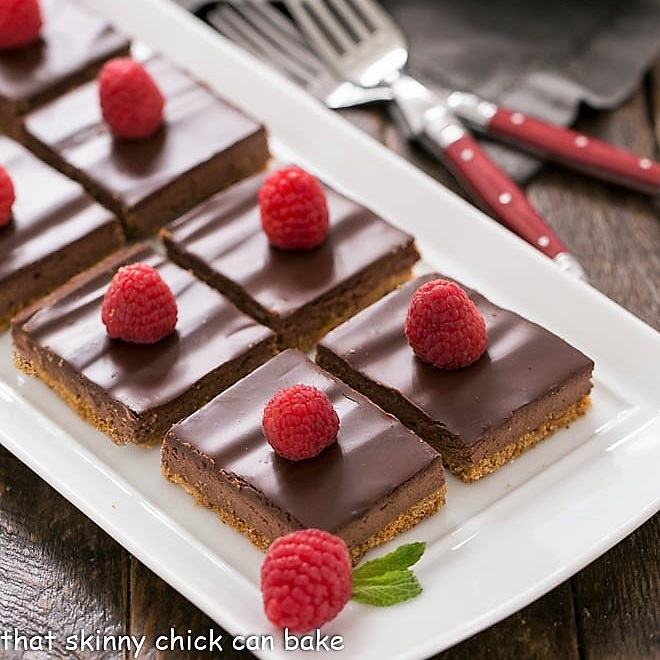dark chocolate mousse bars topped with raspberries on a white ceramic tray
