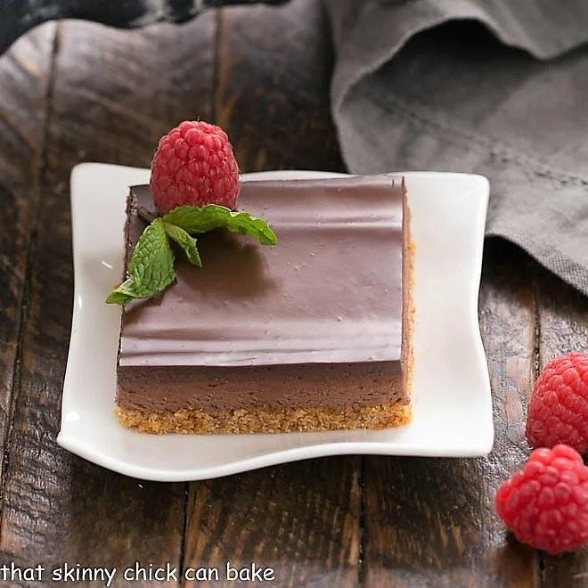 A slice of Dark Chocolate Mousse Bars on a white plate topped with a raspberry