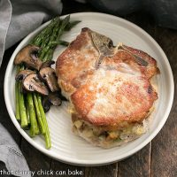Overhead view of stuffed pork chops on a round white plate with asparagus