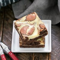 Stack of two Cheesecake Swirl Brownies on a square white plate with two forks
