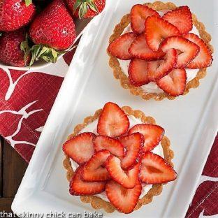 Fresh strawberry tarts on a white serving tray