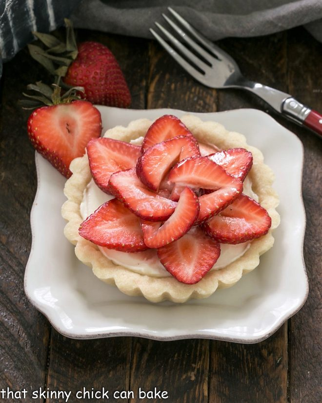 A strawberry tart on a square white plate with a red handled fork