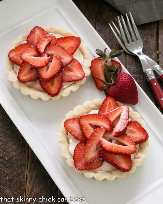 2 fresh strawberry tarts on a white ceramic tray with a strawberry garnish