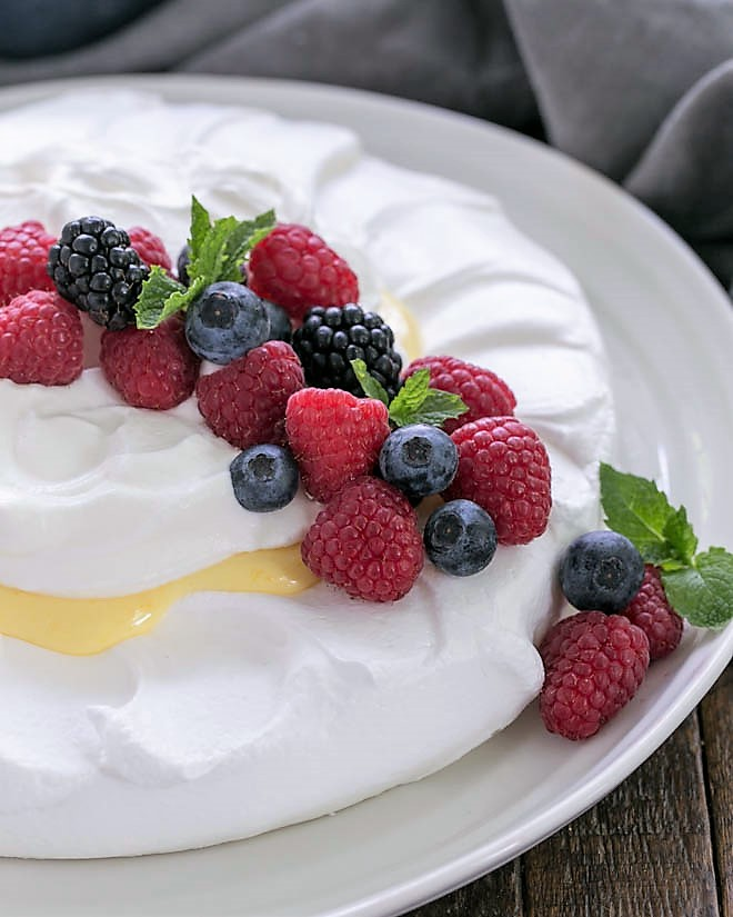 Lemon Pavlova on a white serving plate garnished with berries and mint