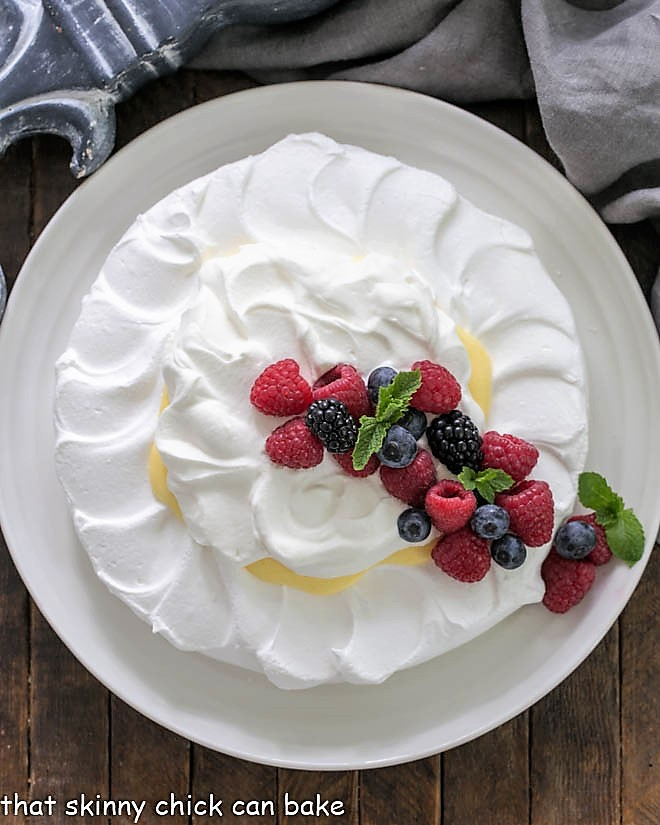 Overhead view of a pavlova dessert topped with lemon cream, whipped cream and berries