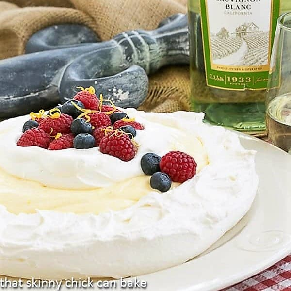 Lemon Pavlova garnished with berries and cream on a white plate