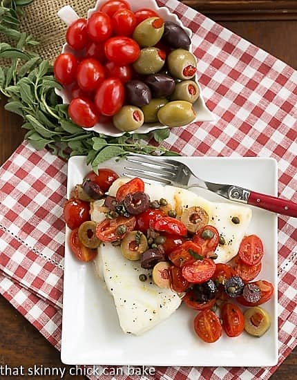Sea Bass with Tomatoes, Olives and Capers on white plate viewed from above