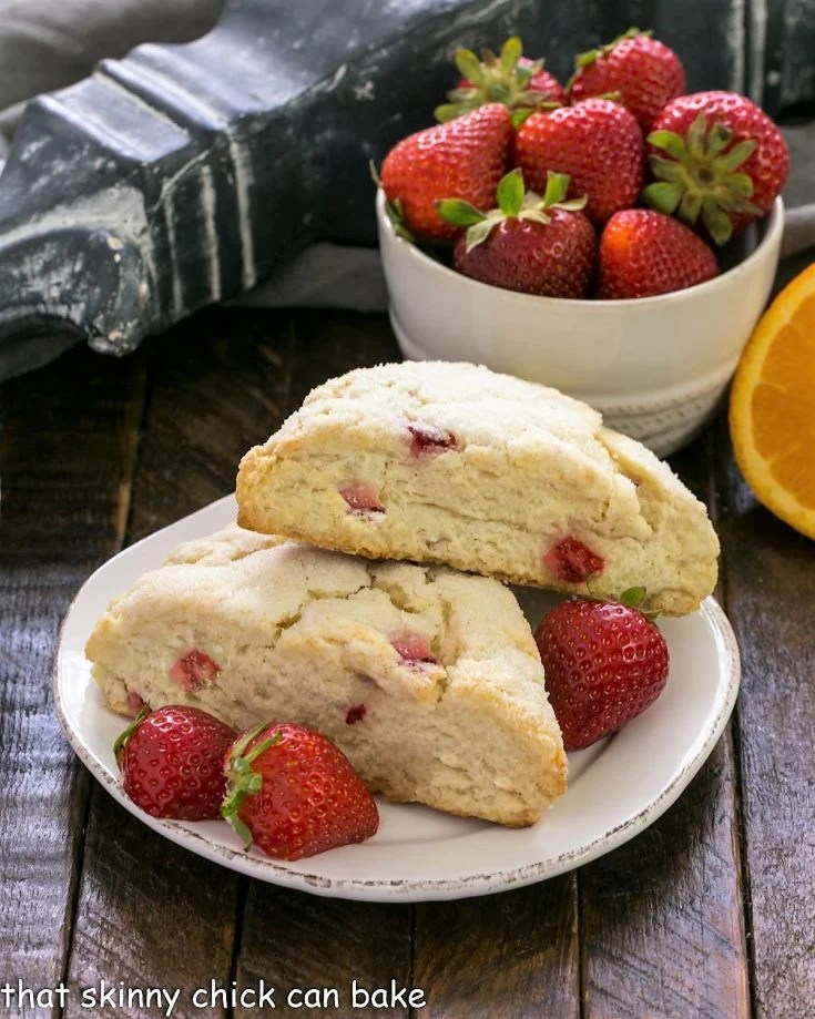 2 scones on a round white plate with fresh strawberries