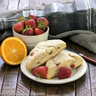 2 strawberry scones on a white plate next to half an orange and a bowl of berries