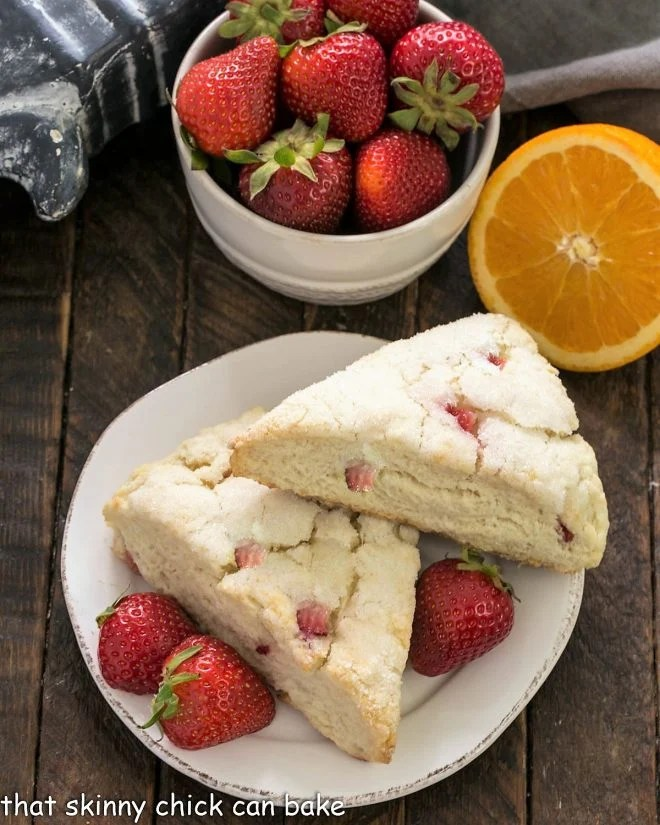 Overhead view of 2 Strawberry Buttermilk Scones on a small white plate with fresh strawberries