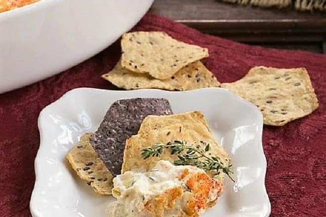 Hot Artichoke Shrimp Dip on a square white plate with chips and a sprig of thyme